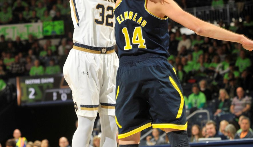 Notre Dame guard Jewell Loyd puts up a shot over Michigan guard Nicole Elmbald, right, in the first half of an NCAA basketball game, Saturday, Dec., 13, 2014, in South Bend, Ind. (AP Photo/Joe Raymond)