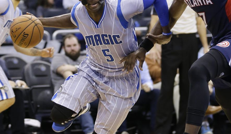 Orlando Magic's Victor Oladipo (5) drives around Atlanta Hawks' Elton Brand, right, during the first half of an NBA basketball game, Saturday, Dec. 13, 2014, in Orlando, Fla. (AP Photo/John Raoux)