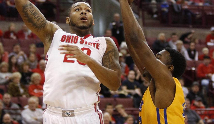 Ohio State's Amir Williams, left, goes up for a shot against Morehead State's Anthony Elechi during the first half of an NCAA college basketball game in Columbus, Ohio, Saturday, Dec. 13, 2014. (AP Photo/Paul Vernon)