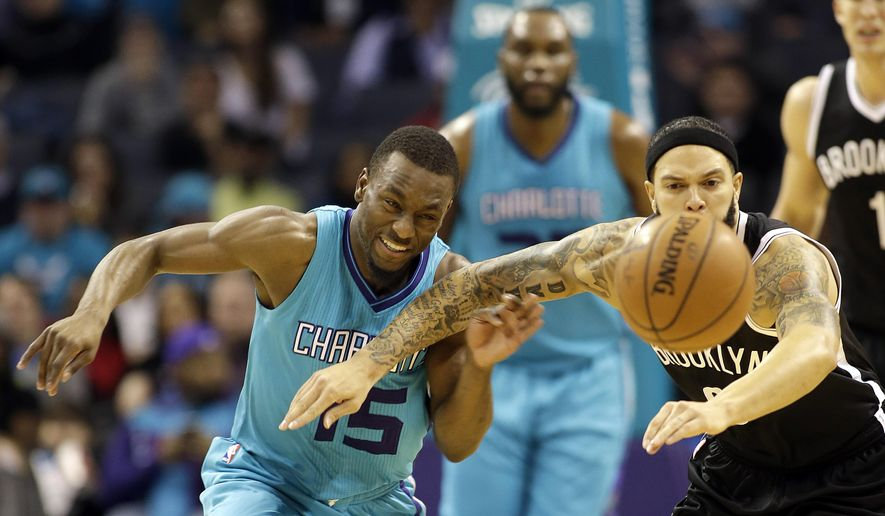 Charlotte Hornets' Kemba Walker, left, tries to wrestle past Brooklyn Nets' Deron Williams, right, for a loose ball during the first half of an NBA basketball game in Charlotte, N.C., Saturday, Dec. 13, 2014. (AP Photo/Bob Leverone)