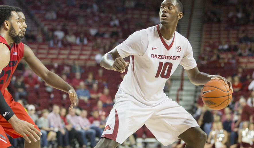 Arkansas forward Bobby Portis, right, looks to pass during second half of an NCAA college basketball game against Dayton on Saturday, Dec. 13, 2014, in Fayetteville, Ark. Arkansas defeated Dayton 69-55. (AP Photo/Gareth Patterson)