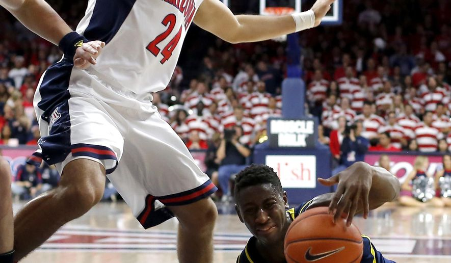 Michigan guard Caris LeVert (23) grabs the loose ball in front of Arizona guard Elliott Pitts (24) during the first half of an NCAA college basketball game, Saturday, Dec. 13, 2014, in Tucson, Ariz. (AP Photo/Rick Scuteri)