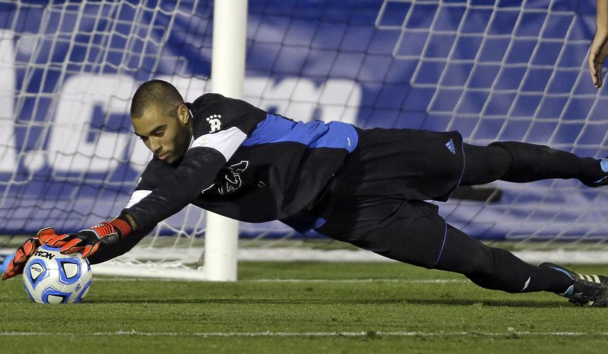 UCLA goalkeeper Earl Edwards Jr. dives to block a shot during the second half of an NCAA College Cup semifinal soccer game against Providence in Cary, N.C., Friday, Dec. 12, 2014. UCLA won 3-2 in overtime. (AP Photo/Gerry Broome)