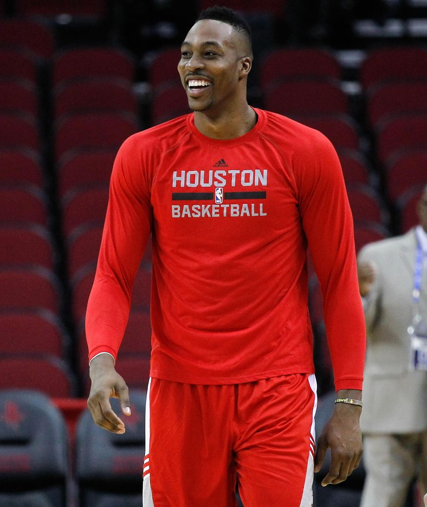 Houston Rockets center Dwight Howard takes the court for warm ups before playing the Denver Nuggets in an NBA basketball game Saturday, Dec. 13, 2014, in Houston. (AP Photo/Bob Levey)