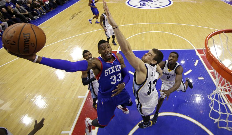 Philadelphia 76ers' Robert Covington, left, goes up for a shot against Memphis Grizzlies' Marc Gasol, of Spain, during the first half of an NBA basketball game, Saturday, Dec. 13, 2014, in Philadelphia. (AP Photo/Matt Slocum)