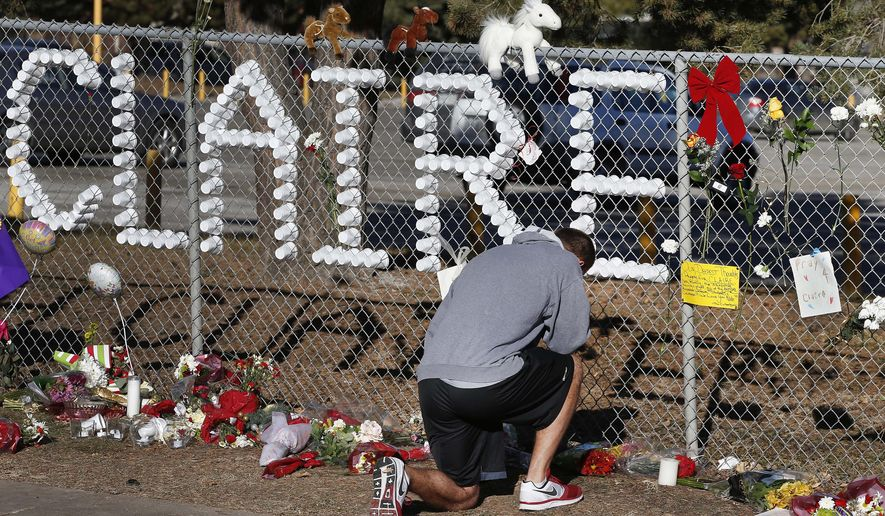 FILE - In this Dec. 16, 2013, file photo, Parker Semin, a 2011 Arapahoe High School graduate, prays at a makeshift memorial bearing the name of student Claire Davis, who was shot by Karl Pierson, a classmate during school three days earlier in an attack, in front of Arapahoe High School in Centennial, Colo.  The father of Pierson posted a newspaper obituary for his son on the first anniversary of the shooting. The Saturday, Dec. 13, 2014 obit came the same day a candlelight vigil will be held for Davis. Mark Pierson said he didn't mean to disrespect the Davis family but wants his son, Karl, remembered as a good son who lost his way for a moment.. (AP Photo/Brennan Linsley, File)
