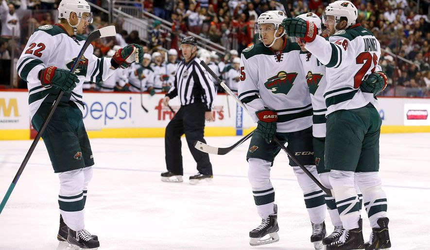Minnesota Wild's Nino Niederreiter (22), of Switzerland, celebrates his goal against the Arizona Coyotes with teammates Thomas Vanek, right, Ryan Suter, second from right, and Jonas Brodin, during the first period of an NHL hockey game Saturday, Dec. 13, 2014, in Glendale, Ariz. (AP Photo/Ross D. Franklin)