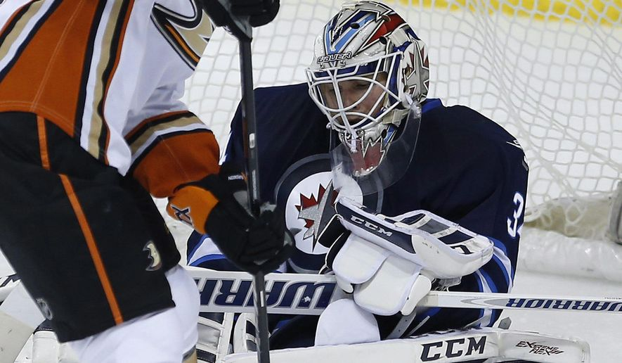 Winnipeg Jets goaltender Michael Hutchinson (34) hangs onto Anaheim Ducks' Rene Bourque's (14) rebound during the first period of their NHL hockey game in Winnipeg, Manitoba, Canada on Saturday, Dec. 13, 2014. (AP Photo/The Canadian Press, John Woods)