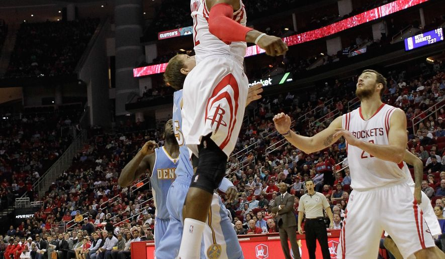 Houston Rockets center Dwight Howard (12) blocks the shot attempt by Denver Nuggets center Timofey Mozgov (25) as forward Donatas Motiejunas (20) looks on in the first half of an NBA basketball game Saturday, Dec. 13, 2014, in Houston. (AP Photo/Bob Levey)