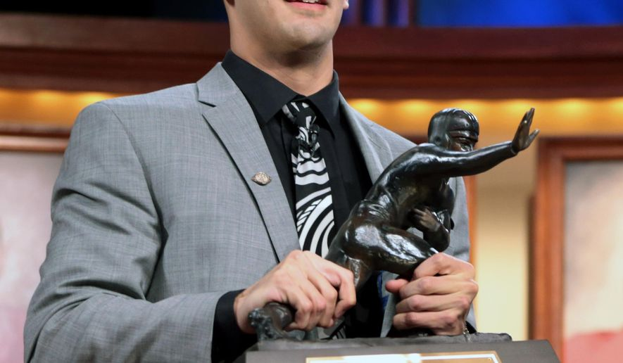 In this photo provided by the Heisman Trust, Oregon quarterback Marcus Mariota holds the Heisman Trophy after being named college football's best player during the Heisman Trophy presentation in New York on Saturday, Dec. 13, 2013. (AP Photo/Heisman Trust, Kelly Kline)