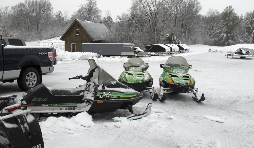 In this Dec. 10, 2014 photo, snowmobiles sit in the yard of  Champlain Valley Motorsports in Cornwall, Vt. The state's snowmobile season is set to open Dec. 16. Snowmobilers say the heavy wet snow that fell this week provided a solid base, but the storm dropped trees that could keep some trails closed until next weekend. (AP Photo/Wilson Ring)