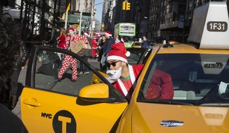 A man dressed in a holiday theme  costume enters a taxi during SantaCon, Saturday, Dec. 13, 2014, in New York. (Associated Press) ** FILE **