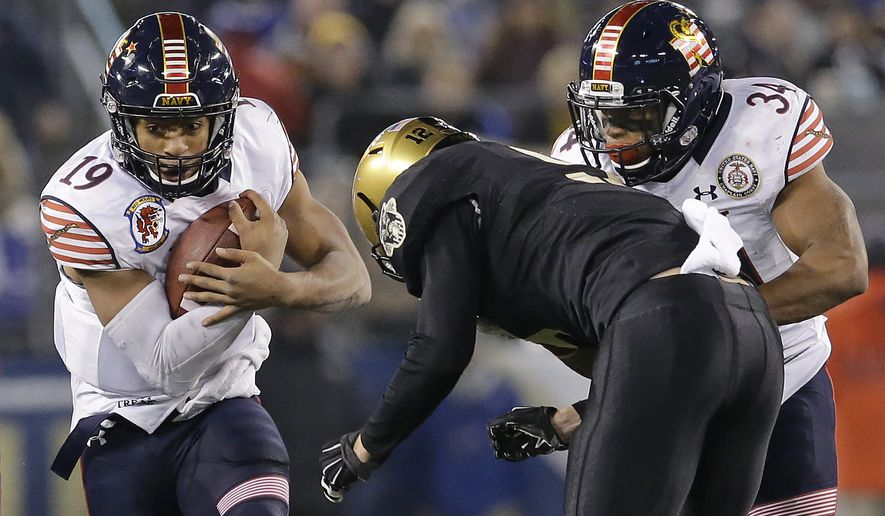 Navy quarterback Keenan Reynolds, left, dodges Army defensive back Hayden Pierce as he rushes the ball past teammate Noah Copeland in the second half of the Army-Navy NCAA college football game, Saturday, Dec. 13, 2014, in Baltimore. Navy won 17-10. (AP Photo/Patrick Semansky)