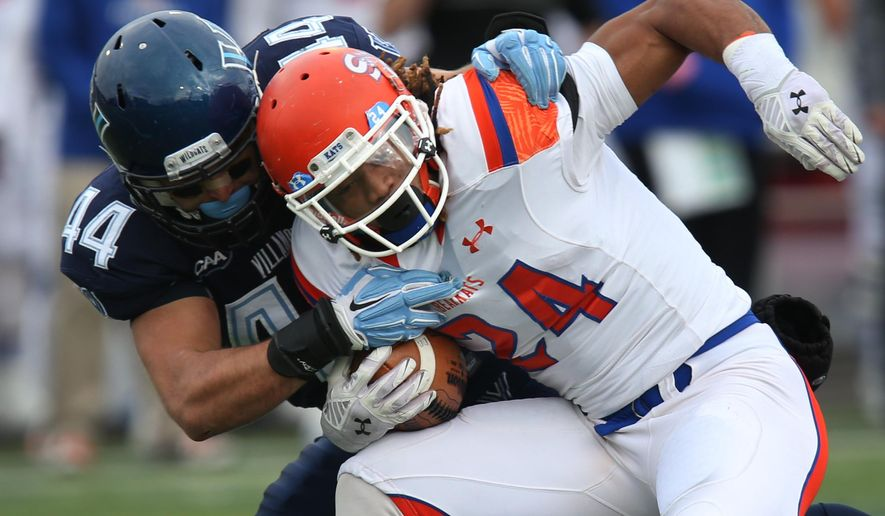 Sam Houston State running back Donavan Williams (24) is tackled by Villanova linebacker Don Cherry (44) in the first quarter of an FCS quarterfinal NCAA college football game, Saturday, Dec. 13, 2014, in Villanova, Pa. (AP Photo/Laurence Kesterson)