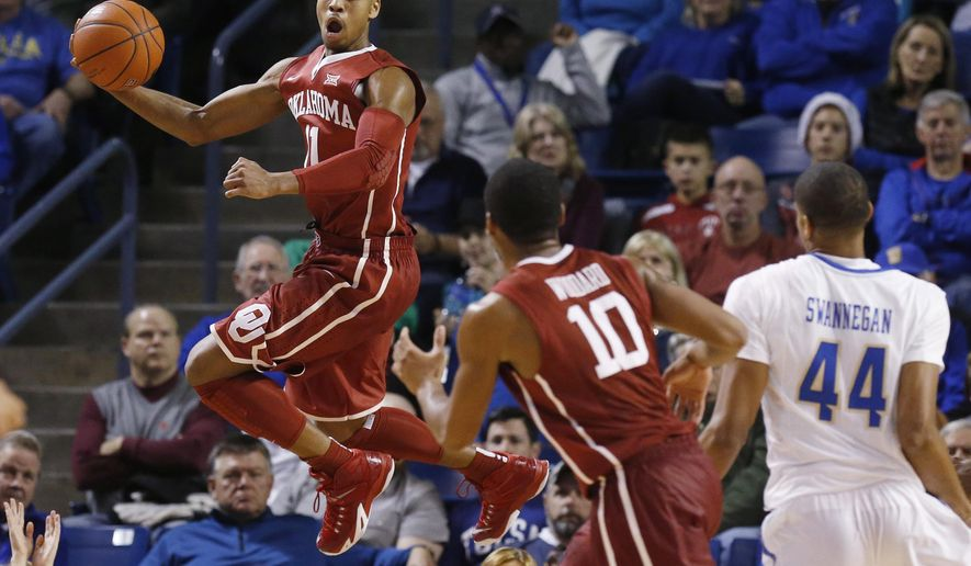 Oklahoma guard Isaiah Cousins (11) jumps up to keep the ball in bounds in the first half of an NCAA college basketball game against Tulsa in Tulsa, Okla., Saturday, Dec. 13, 2014. Oklahoma won 87-68. (AP Photo/Sue Ogrocki)