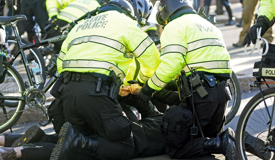 Police arrest a protester as hundreds march in Boston in a national protest of police killings of unarmed black men, Saturday, Dec. 13, 2014. (AP Photo/The Boston Herald, Faith Ninivaggi)  BOSTON GLOBE OUT; METRO BOSTON OUT; MAGS OUT; ONLINE OUT