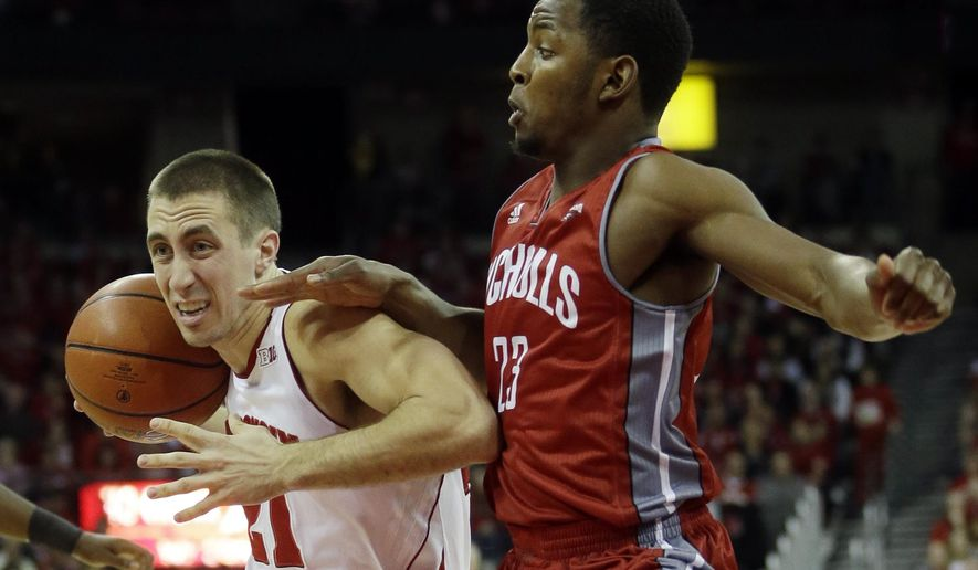 Wisconsin's Josh Gasser (21) tries to drive past Nicholls State's Quinton Thomas during the first half of an NCAA college basketball game Saturday, Dec. 13, 2014, in Madison, Wis. (AP Photo/Morry Gash)