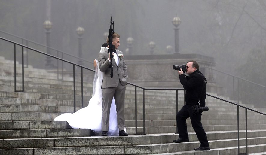 "A groom holds an AR-10 rifle as he stands with his bride while the party was having their pre-wedding portraits taken on the steps of the capitol before a rally nearby by gun-rights advocates to protest a new expanded gun background check law in Washington state Saturday, Dec. 13, 2014, in Olympia, Wash. The wedding party was not part of the protest, but posed for pictures with it after being handed it by gun activist Brandon Lyons, who said ""we've all just broken the law,"" by handing the gun over. Saturday's protest was called the ""I Will Not Comply"" rally, and those attending said they will openly exchange firearms in opposition to the state's new voter-approved universal background check law, Initiative 594. The law, which took effect on Dec. 4, requires background checks on all sales and transfers, including private transactions and many loans and gifts. (AP Photo/Elaine Thompson)"