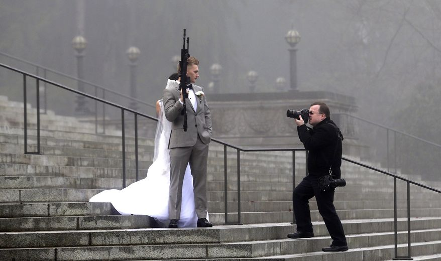 """A groom holds an AR-10 rifle as he stands with his bride while the party was having their pre-wedding portraits taken on the steps of the capitol before a rally nearby by gun-rights advocates to protest a new expanded gun background check law in Washington state Saturday, Dec. 13, 2014, in Olympia, Wash. The wedding party was not part of the protest, but posed for pictures with it after being handed it by gun activist Brandon Lyons, who said """"we've all just broken the law,"""" by handing the gun over. Saturday's protest was called the """"I Will Not Comply"""" rally, and those attending said they will openly exchange firearms in opposition to the state's new voter-approved universal background check law, Initiative 594. The law, which took effect on Dec. 4, requires background checks on all sales and transfers, including private transactions and many loans and gifts. (AP Photo/Elaine Thompson)"""