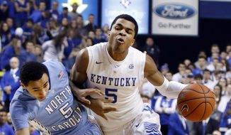 North Carolina's Marcus Paige, left, draws a charging foul on Kentucky's Andrew Harrison during the first half of an NCAA college basketball game, Saturday, Dec. 13, 2014. (AP Photo/James Crisp)