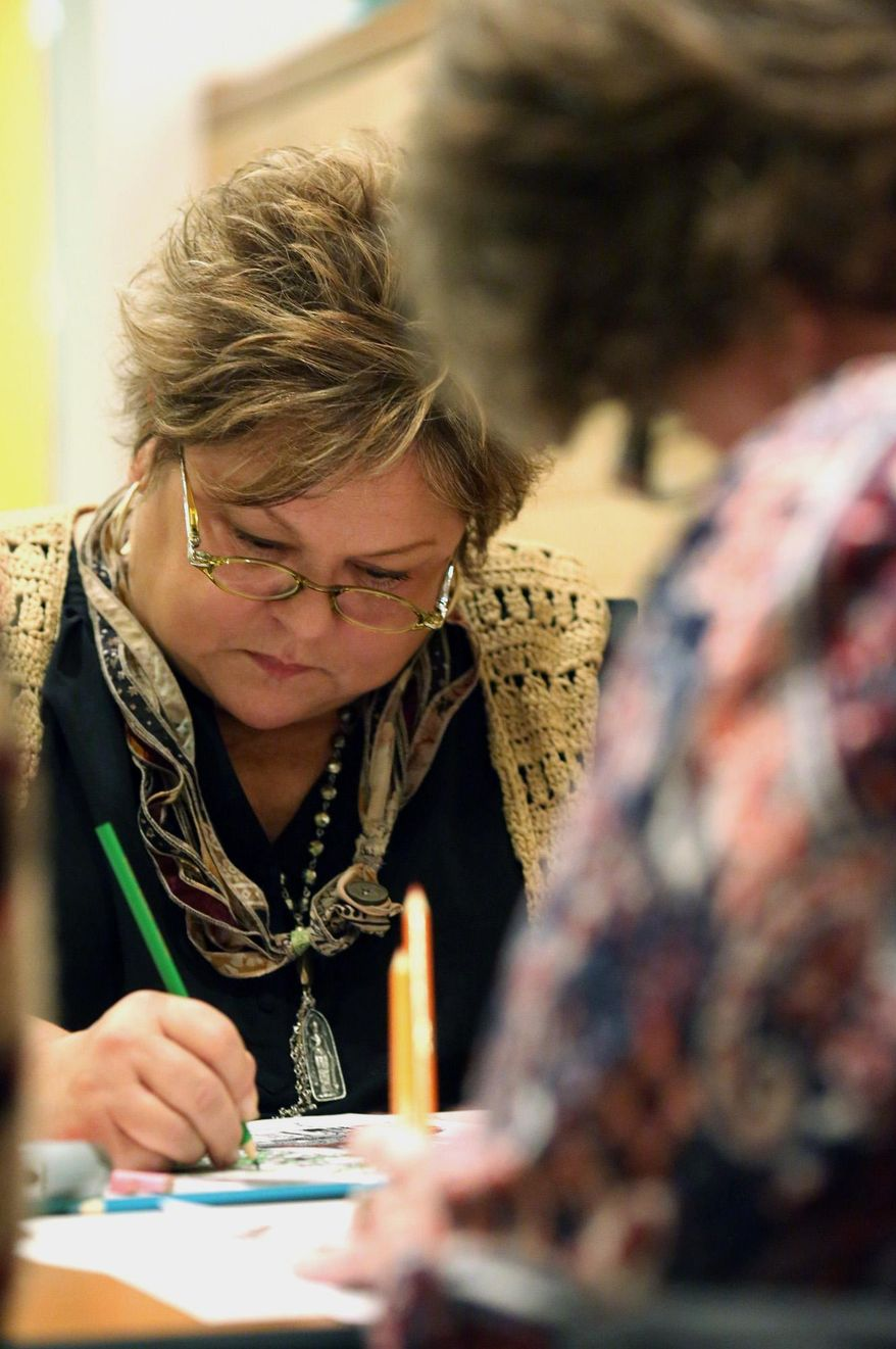 """This photo taken Nov. 20, 2014, Diane Lazor focuses on a page during an adult coloring night at the Market 65 restaurant in Columbus, Ohio. The evening was created to promote """"The Columbus Ohio Coloring and Activity Book"""" created by Katie Barron. The book features various Columbus scenes that encourage the artist to color in their own ideas about what shade the subject should be. The adult coloring nights allow guests to drink wine and talk while they color the pages. (AP Photo/The Columbus Dispatch, Brooke LaValley)"""