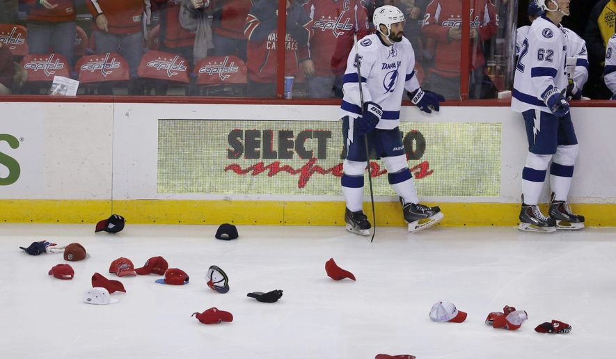 Tampa Bay Lightning defensemen Jason Garrison (5) and Andrej Sustr (62), from the Czech Republic, pause near the bench as hats collect on the ice after the third goal by Washington Capitals center Nicklas Backstrom, from Sweden, for a hat trick in the third period of an NHL hockey game, Saturday, Dec. 13, 2014, in Washington. The Capitals won 4-2. (AP Photo/Alex Brandon)