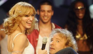 "FILE - In this Nov. 5, 2005 file photo shows U.S. singer Madonna puts her leg on the shoulder of German TV host Thomas Gottschalk during the German TV show 'Wetten dass, ...?' ('Bet it ...') in southwestern German city of Mannheim. ""Wetten, dass...."" - Germany's most successful TV show - will be televised for the last time on Saturday, Dec. 13, 2014.  Since its start in 1981 the show has been a magnet for international entertainment stars and had more than 20 million viewers per show in the 1980s.   (AP Photo/Alex Grimm, Pool)"