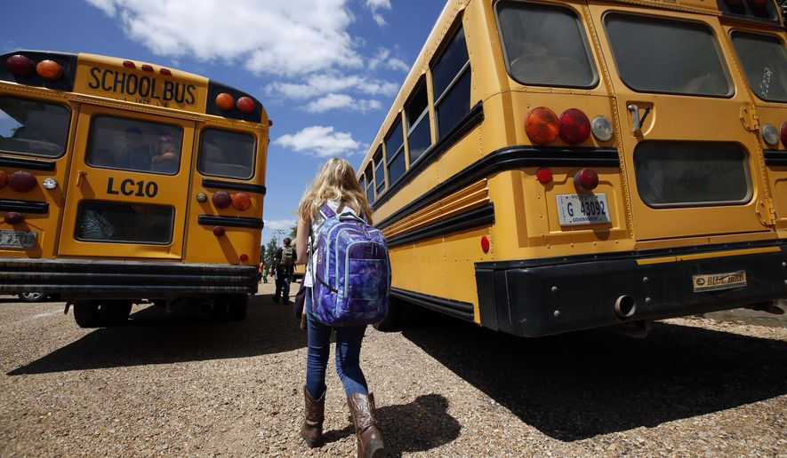 In this Aug. 13, 2014 file photograph, a student prepares to leave the Enterprise Attendance Center, southeast of Brookhaven Miss. (AP Photo/Rogelio V. Solis) ** FILE **