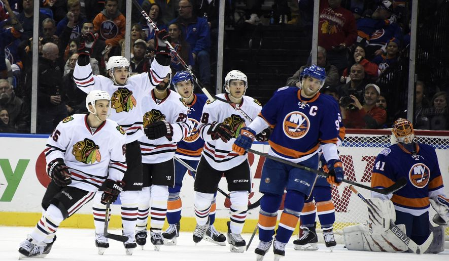 Chicago Blackhawks center Andrew Shaw (65), defenseman Johnny Oduya (27) and teammates celebrate left wing Daniel Carcillo's goal as New York Islanders center John Tavares (91) and goalie Jaroslav Halak (41) react in the second period of an NHL hockey game on Saturday, Dec. 13, 2014, in Uniondale, N.Y. (AP Photo/Kathy Kmonicek)