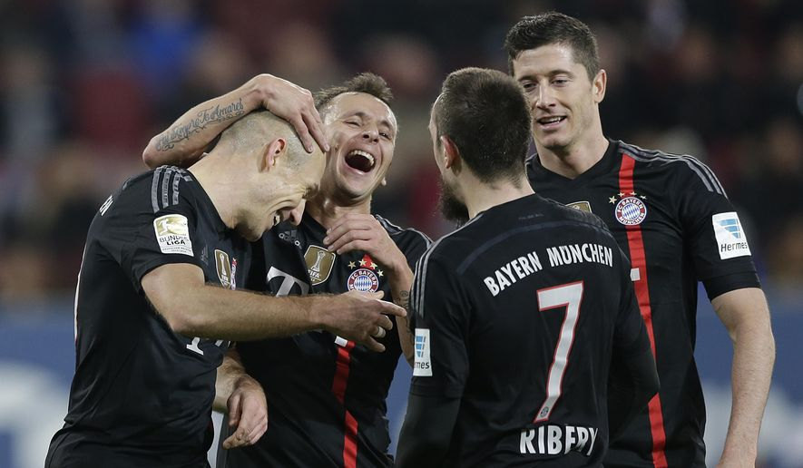 Bayern's Arjen Robben from the Netherlands, from left, celebrates with teammate Rafinha from Brazil, Franck Ribery from France and Robert Lewandowski from Poland  after scoring his side's fourth goal during the German first division Bundesliga soccer match between FC Augsburg and FC Bayern Munich in the SGL Arena in Augsburg, Germany, on Saturday, Dec. 13, 2014. (AP Photo/Matthias Schrader)