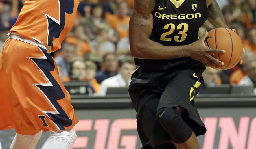 Oregon forward Elgin Cook (23) drives to the basket against Illinois guard Kendrick Nunn, left, during the first half of an NCAA college basketball game in Chicago on Saturday, Dec. 13, 2014. (AP Photo/Nam Y. Huh)