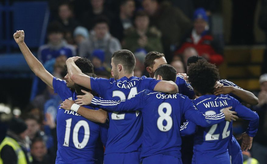 Chelsea's Diego Costa, left,  is mobbed by his teammates after scoring his sides second goal during their English Premier League soccer match between Chelsea and Hull City at Stamford Bridge stadium in London, Saturday, Dec 13, 2014. (AP Photo/Alastair Grant)