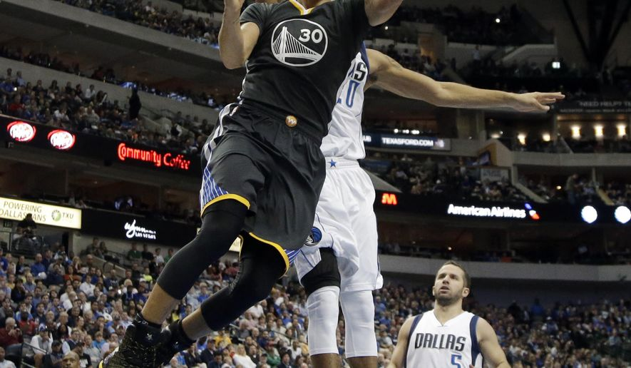 Golden State Warriors guard Stephen Curry (30) gets by Dallas Mavericks' Devin Harris, rear, for a reverse layup in the first half of an NBA basketball game, Saturday, Dec. 13, 2014, in Dallas. The Mavericks' J.J. Barea (5) of Puerto Rico- watches the shot. (AP Photo/Tony Gutierrez)