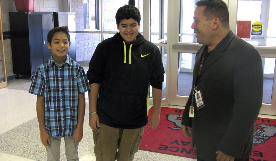 ADVANCE FOR USE SUNDAY, DEC. 14 - In this photo taken on Dec. 4, 2014, Hampton-Dumont Middle School Principal Tony Spradlin talks with his mentees Daniel Sanchez Garcia, left, seventh grade; and Alex Van Cleave, eighth grade, in Hampton Iowa. Spradlin is a mentor for three students through a new program targeting Latino students called Al Exito (to success.) (AP Photo/The Globe-Gazette, Laura Bird)