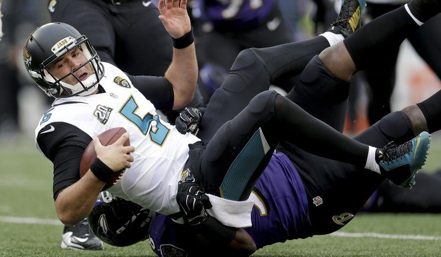 Jacksonville Jaguars quarterback Blake Bortles (5) is sacked by Baltimore Ravens outside linebacker Elvis Dumervil (58) during the first half of an NFL football game in Baltimore, Sunday, Dec. 14, 2014. (AP Photo/Patrick Semansky)