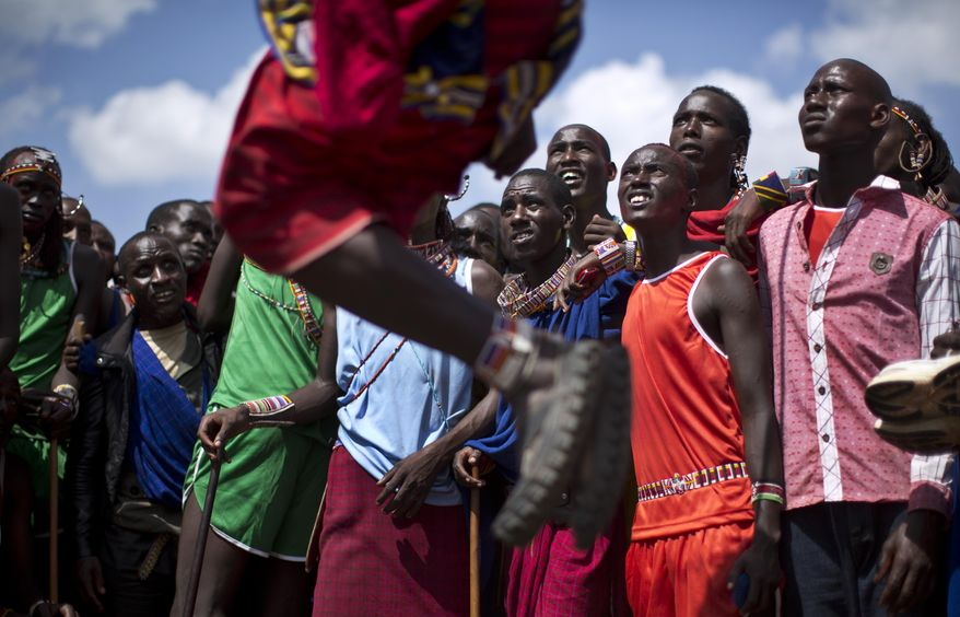 Maasai warriors look up as a competitor makes the high jump, in which athletes must touch a high line with the top of their heads, at the annual Maasai Olympics in the Sidai Oleng Wildlife Sanctuary near to Mt. Kilimanjaro, southern Kenya, Saturday, Dec. 13, 2014. Maasai men and women from the Amboseli and Tsavo region compete for medals and prizes in the event which aims for a sports competition of Maasai skills such as running, jumping, and throwing, to replace lion-hunting as the traditional warrior activity. (AP Photo/Ben Curtis)