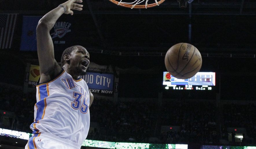 Oklahoma City Thunder forward Kevin Durant (35) shouts as he dunks against the Phoenix Suns in the second quarter of an NBA basketball game in Oklahoma City, Sunday, Dec. 14, 2014. (AP Photo/Sue Ogrocki)