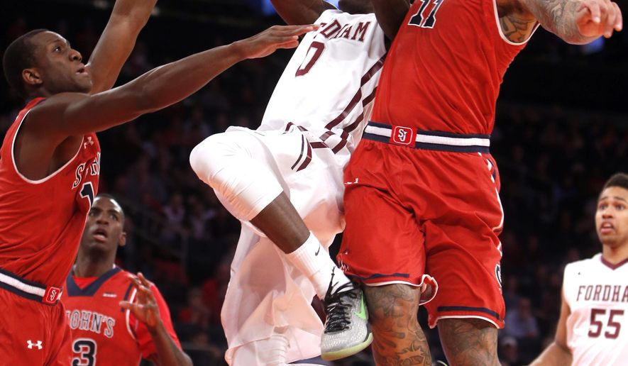 Fordham's Antwoine Anderson (0) is double-teamed by St. John's Phil Greene IV, left, and D'Angelo Harrison (11) during the first half of an NCAA college basketball game Sunday, Dec. 14, 2014, in New York. (AP Photo/Jason DeCrow)