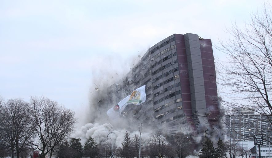 The North Park Plaza building is imploded on Sunday, Dec. 14, 2014 in Southfield, Mich. Oakland Community College owns the property just north of Detroit and auctioned off the chance to blow it up to the highest bidder. The college bought the 42-year-old building earlier this year and says it has no immediate plans for the land. (AP Photo/Detroit Free Press, Tim Galloway)  DETROIT NEWS OUT;  NO SALES