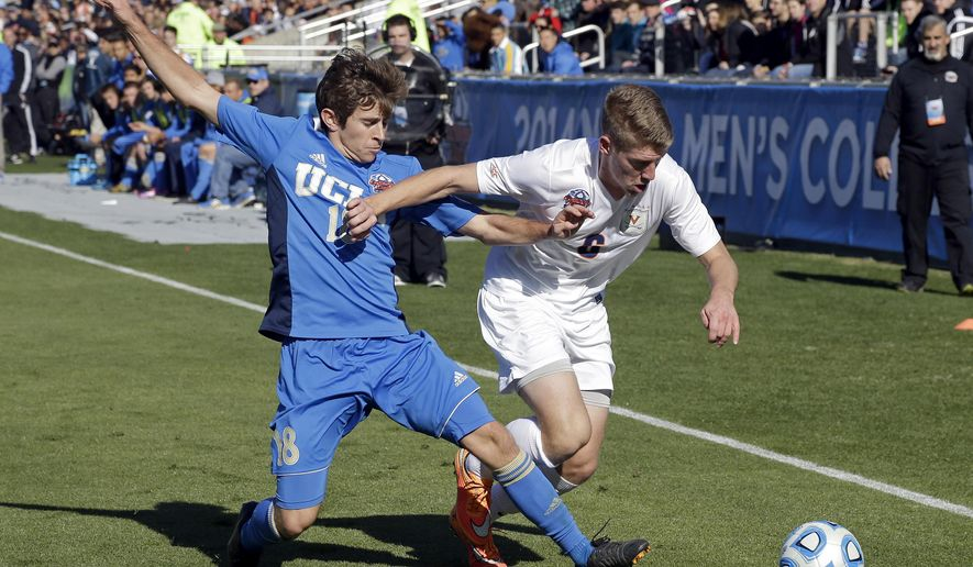 UCLA's Brian Iloski and Virginia's Scott Thomsen (6) chase the ball during the first half of an NCAA College Cup championship soccer game in Cary, N.C., Sunday, Dec. 14, 2014. (AP Photo/Gerry Broome)