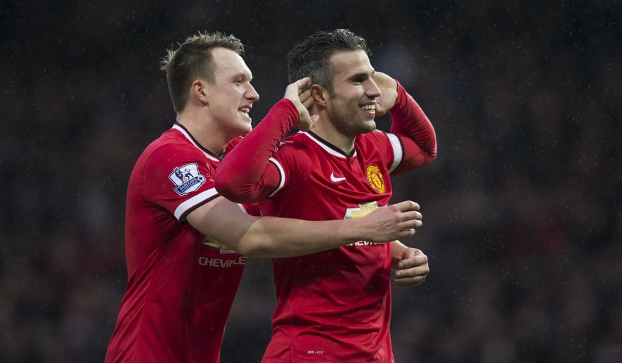 Manchester United's Robin van Persie, right, celebrates with teammate Phil Jones after scoring during the English Premier League soccer match between Manchester United and Liverpool at Old Trafford Stadium, Manchester, England, Sunday Dec. 14, 2014. (AP Photo/Jon Super)