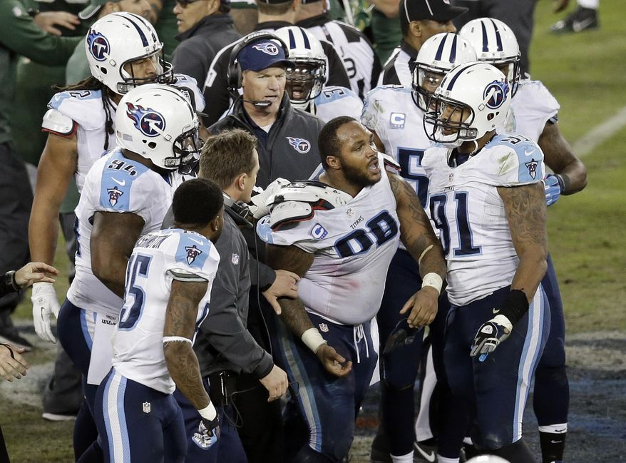 Tennessee Titans defensive end Jurrell Casey (99) is restrained by head coach Ken Whisenhunt, center, during a fight in the second half of an NFL football game between the Titans and the New York Jets, Sunday, Dec. 14, 2014, in Nashville, Tenn. (AP Photo/James Kenney)