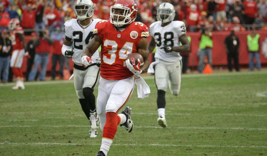 Kansas City Chiefs running back Knile Davis (34) runs for a touchdown ahead of Oakland Raiders free safety Charles Woodson (24) and cornerback T.J. Carrie (38) during the second half of an NFL football game in Kansas City, Mo., Sunday, Dec. 14, 2014. (AP Photo/Charlie Riedel)
