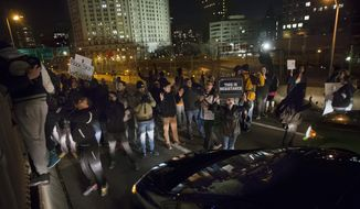 Demonstrators march over the inbound lane of the Brooklyn Bridge in New York, Saturday, Dec. 13, 2014, during the Justice for All rally and march. In the past three weeks, grand juries have decided not to indict officers in the chokehold death of Eric Garner in New York and the fatal shooting of Michael Brown in Ferguson, Mo. The decisions have unleashed demonstrations and questions about police conduct and whether local prosecutors are the best choice for investigating police. (AP Photo/John Minchillo)