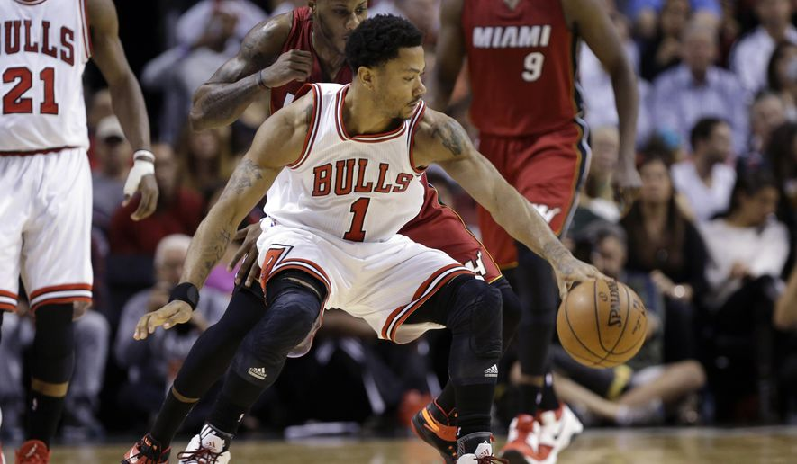 Chicago Bulls' Derrick Rose (1) drives to the basket as the Miami Heat's Mario Chalmers, left, defends in the first half of an NBA basketball game, Sunday, Dec. 14, 2014, in Miami. (AP Photo/Lynne Sladky)
