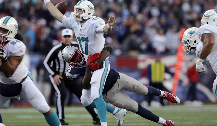 New England Patriots defensive end Chandler Jones, rear, sacks Miami Dolphins quarterback Ryan Tannehill in the second half of an NFL football game, Sunday, Dec. 14, 2014, in Foxborough, Mass. Miami recovered the fumble. (AP Photo/Charles Krupa)