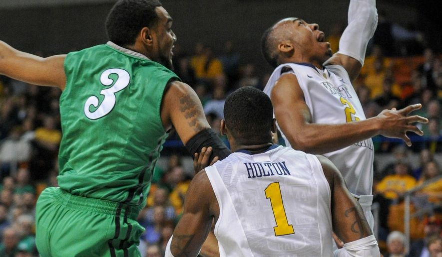 West Virginia's Jevon Carter (2) shoots as Marshall's Jay Johnson (3) defends during the first half of an NCAA college basketball game in Charleston, W.Va., on Sunday, Dec. 14, 2014. (AP Photo/Tyler Evert)