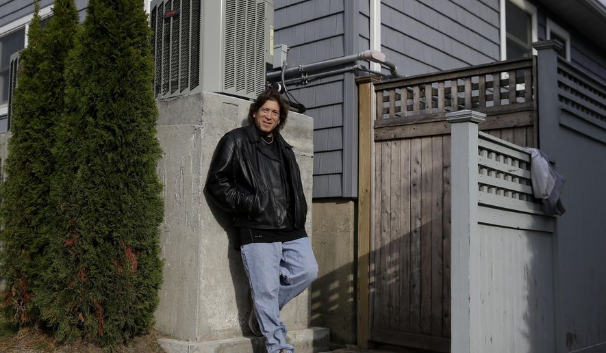 In this Monday, Dec. 1, 2014 photo, Jordan Farkas poses for a picture next to his air conditioner, which is raised eight feet above street level to prevent flooding damage, in Long Beach, N.Y. Some homeowners whose property was ravaged by Superstorm Sandy say they are being denied assistance from other programs because they took out low-interest federal loans right after the storm on the advice of federal workers. (AP Photo/Seth Wenig)