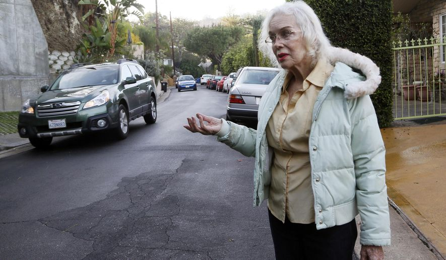 "In t Thursday, Dec. 4, 2014 photo resident Paula Hamilton stands on a street outside her house in the Sherman Oaks section of Los Angeles. ""The traffic is unbearable now. You can't even walk your dog,"" said Hamilton, who lives on a once quiet little street. When the people whose houses hug the narrow warren of streets paralleling the busiest urban freeway in America began to see bumper-to-bumper traffic rushing by their homes a year or so ago they were baffled. When word spread that the explosively popular new smartphone app Waze was sending many of those cars through their neighborhood in a quest to shave five minutes off a daily rush-hour commute, they were angry and ready to fight back. (AP Photo/Nick Ut)"