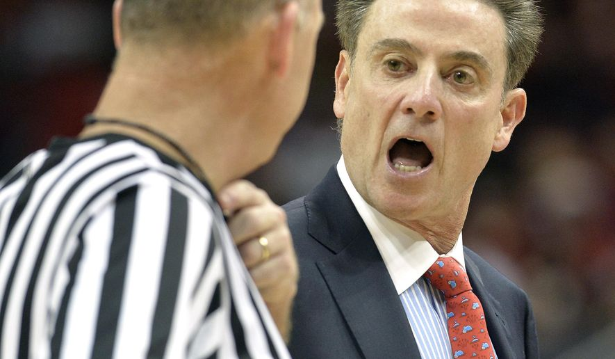 Louisville head coach Rick Pitino, right, argues a call with official Tim Clougherty during the second half of an NCAA college basketball game against UNC Wilmington, Sunday, Dec. 14, 2014, in Louisville, Ky. Louisville won 68-57. (AP Photo/Timothy D. Easley)